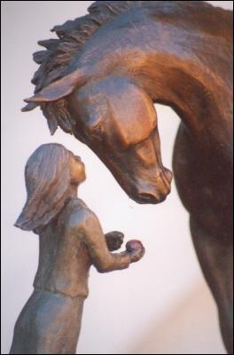 Horse sculpture of young girl feeding her horse an apple.  Sculpture titled First Love